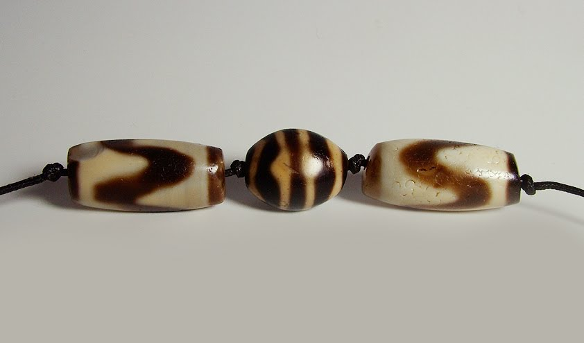 A large matched pair of ancient Tasso dZi beads flank an ancient Tiger dZi.
